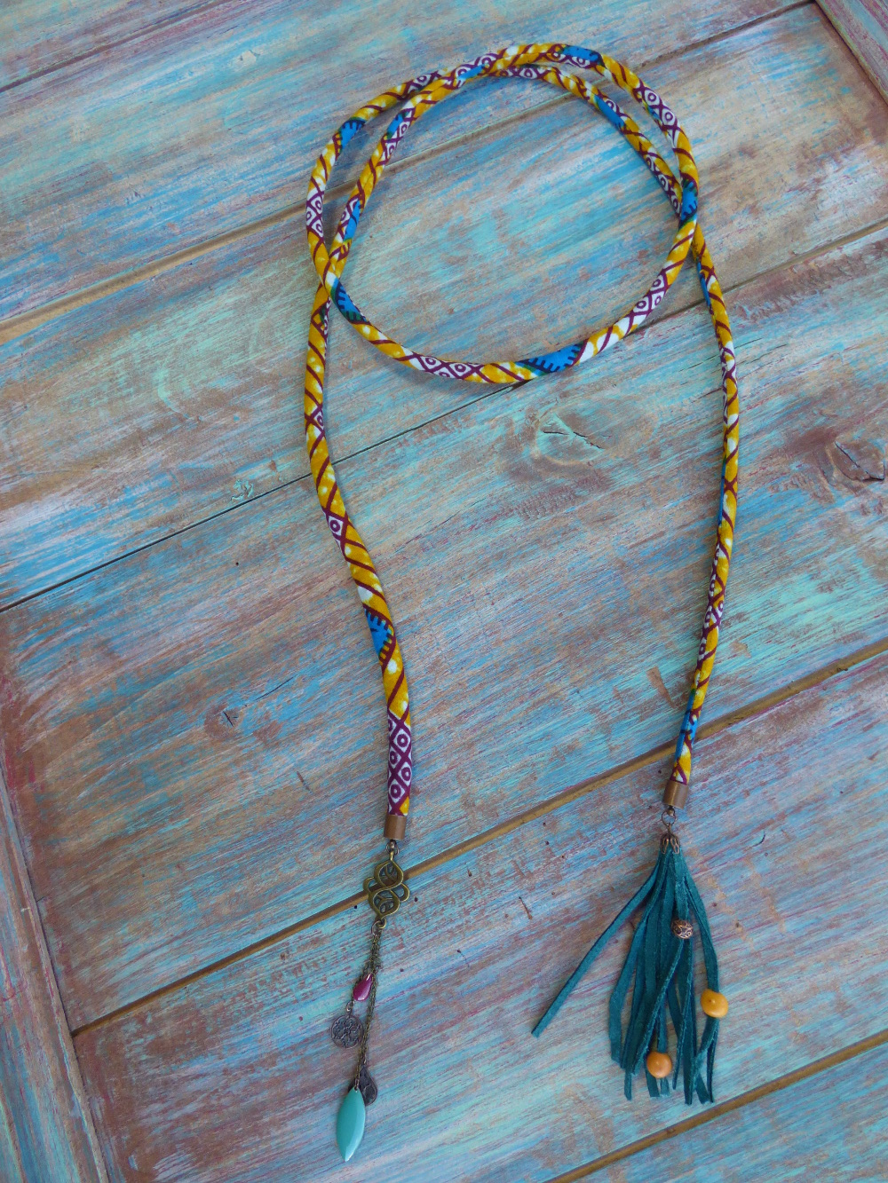 Collier ethnique à enrouler autour du cou en cordon en wax jaune et pompon en cuir bleu.