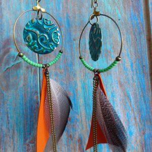 Boucles d'oreilles créoles au style bohème en laiton, plumes et cuir orange.